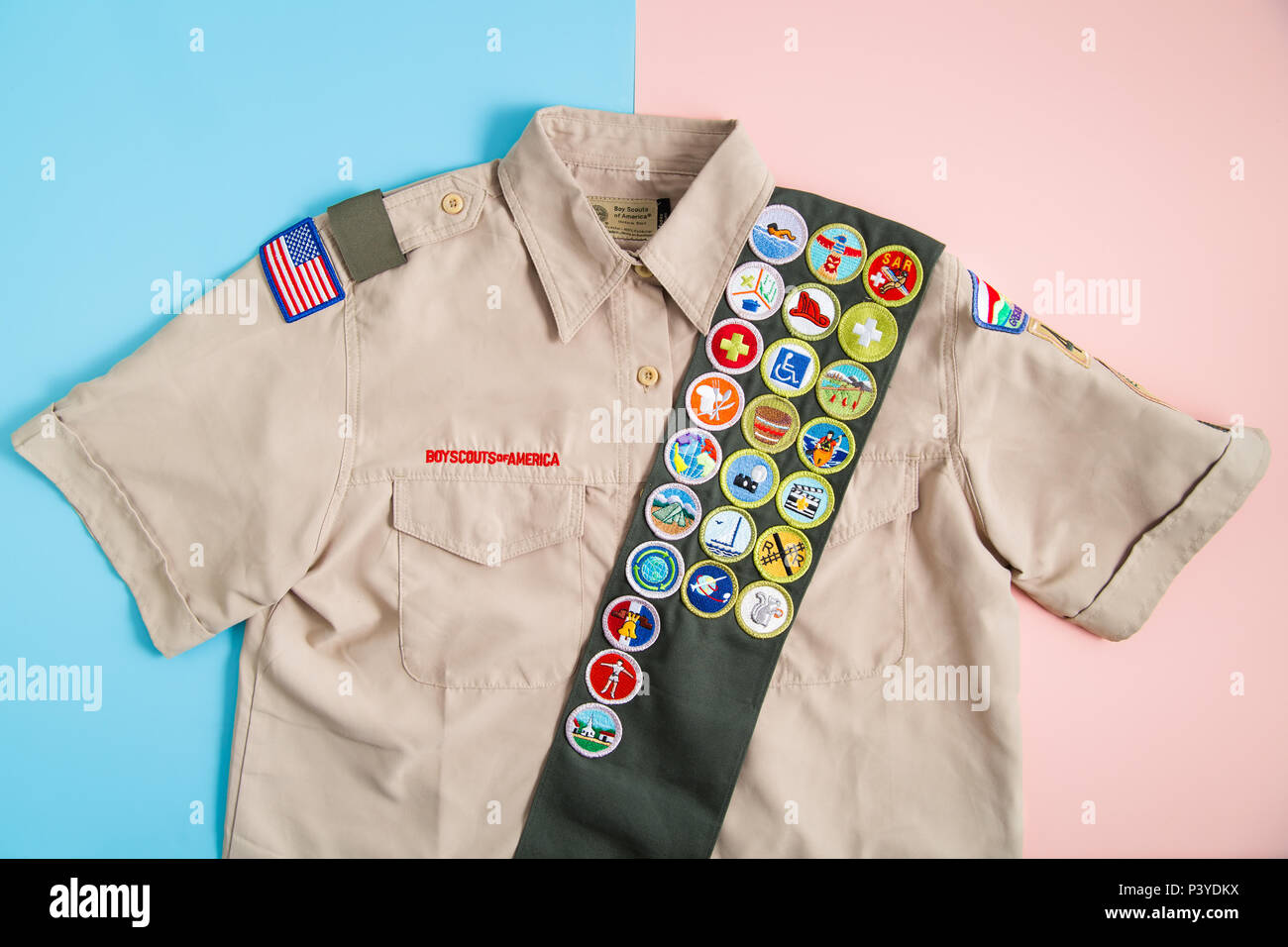 SAINT LOUIS, UNITED STATES - MAY 3, 2018:  Boy Scouts of America (BSA) uniform shirt and merit badge sash on pink and blue background as BSA welcomes  - Stock Image