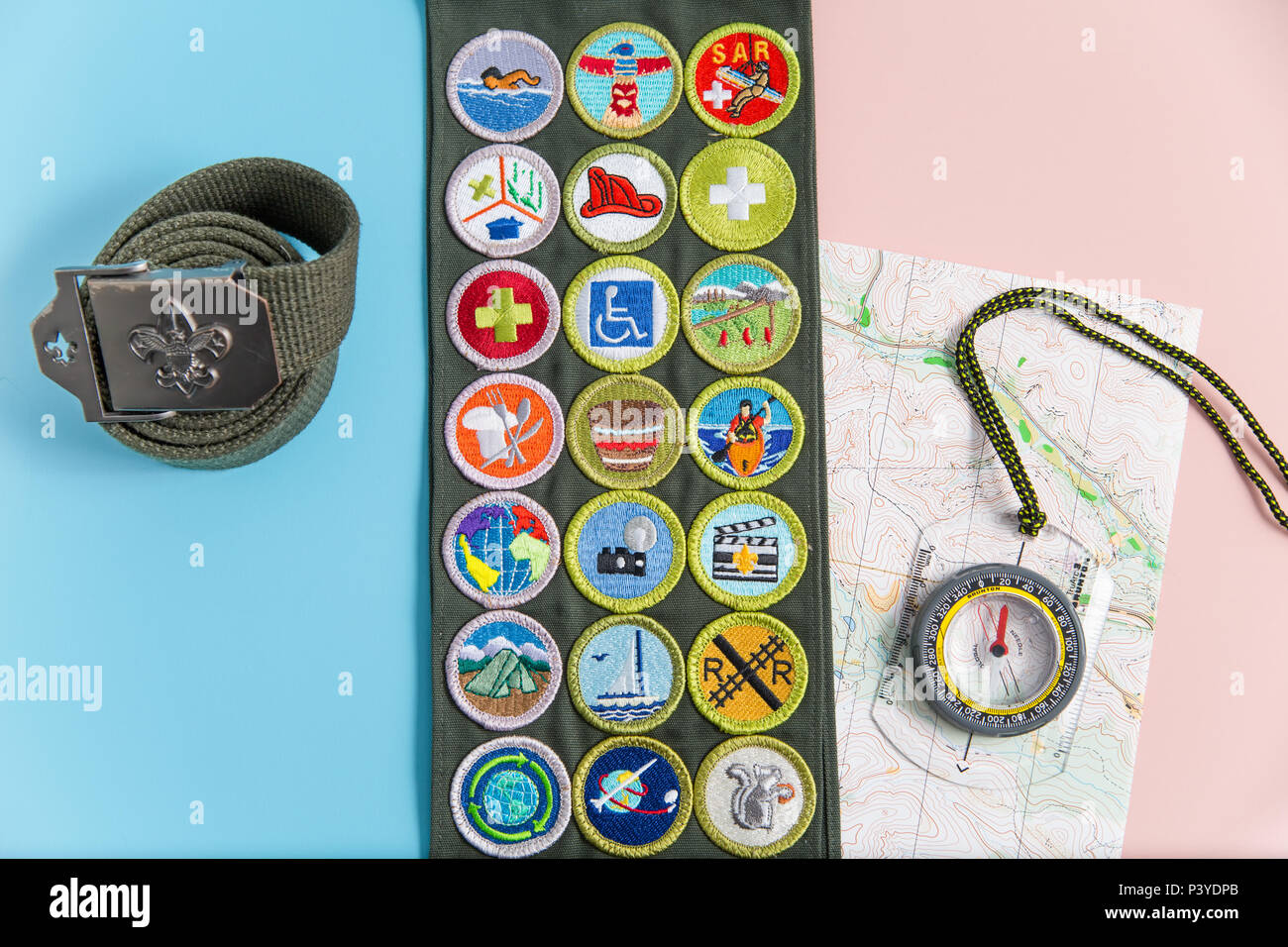 SAINT LOUIS, UNITED STATES - MAY 3, 2018:  Boy Scouts of America (BSA) merit badge sash, belt, compass, and map on pink and blue background as BSA wel - Stock Image
