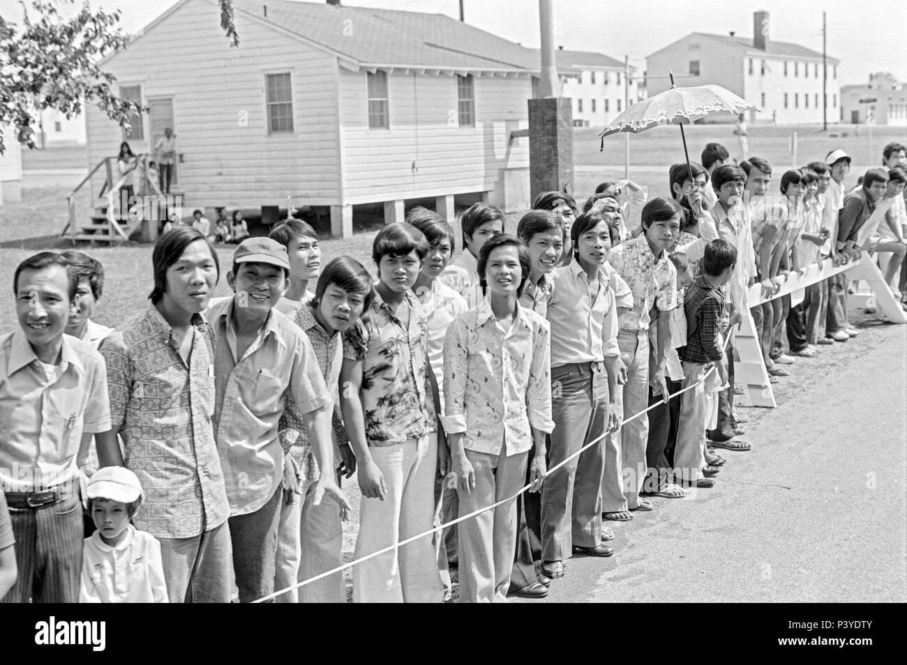 FORT SMITH, AR, USA - AUGUST 10, 1975 -- A line of newly-arrived Vietnamese refugees stand and wait for the passing of President Gerald Ford.  The president is to be touring the Fort Chaffee Vietnamese refugee center and welcoming the evacuated South Vietnamese to the United States.  Behind the people stands rows of the barracks buildings that housed the refugees. - Stock Image