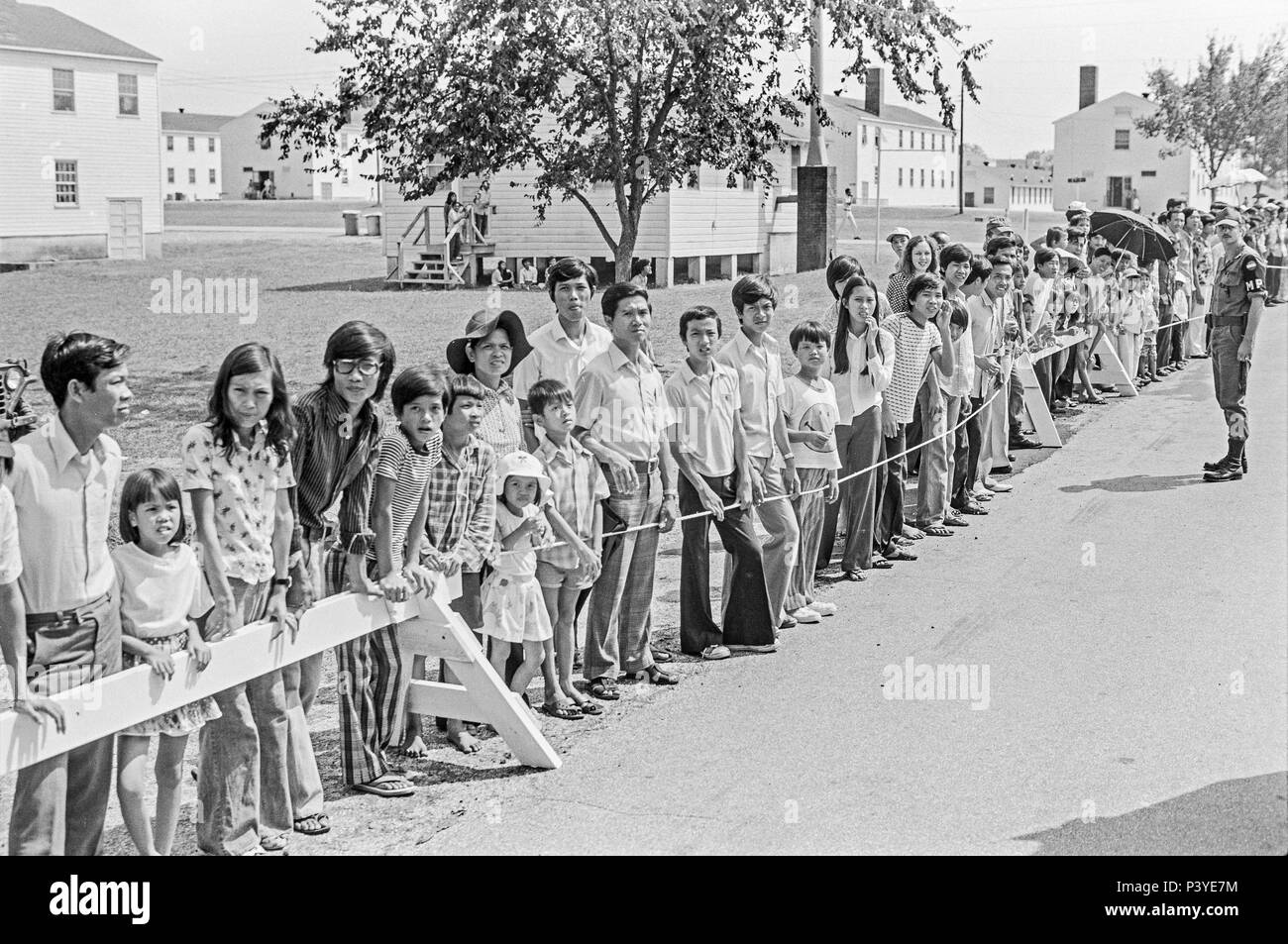 FORT SMITH, AR, USA - AUGUST 10, 1975 -- A military policeman watches as a  line of newly-arrived Vietnamese refugees stand and wait for the passing of President Gerald Ford.  The president is to be touring the Fort Chaffee Vietnamese refugee center and welcoming the evacuated South Vietnamese to the United States.  Behind the people stands rows of the barracks buildings that housed the refugees. - Stock Image