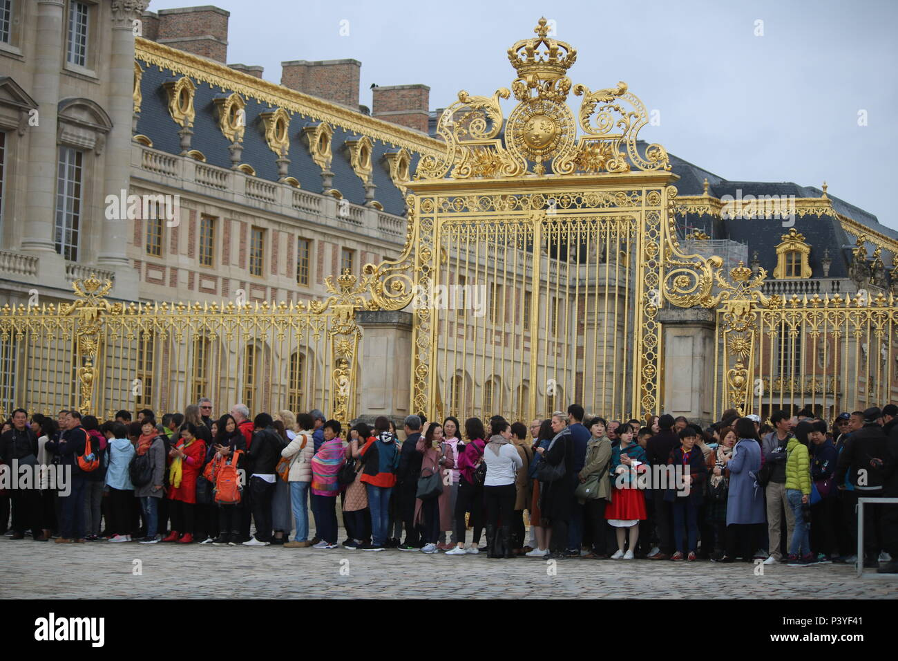 Too many tourists - large queue of tourists in front of golden gates of Versailles - Stock Image