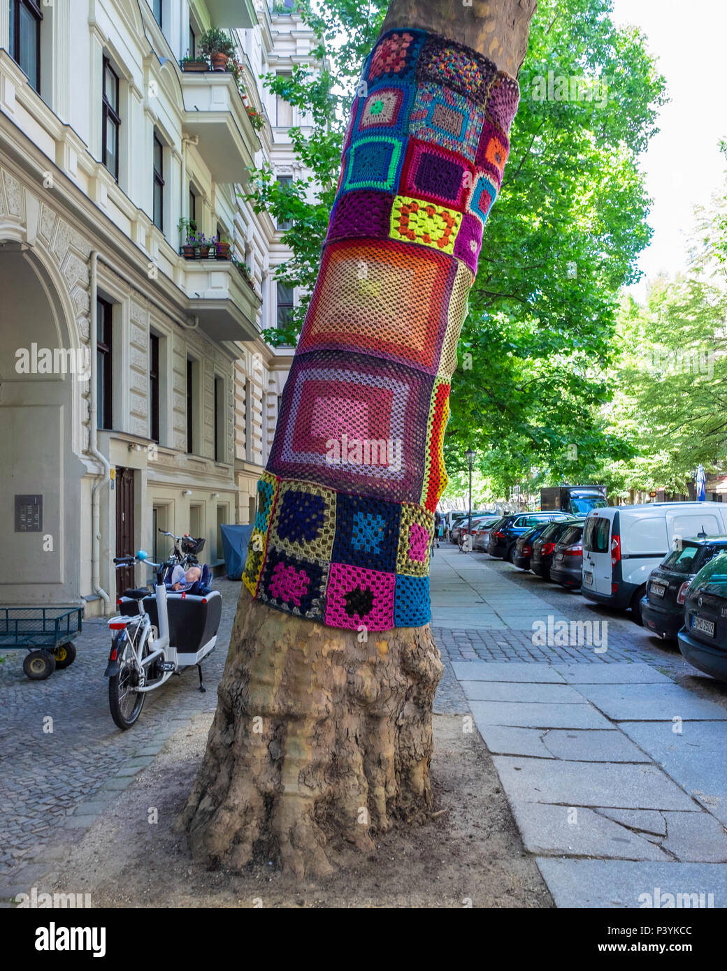 Berlin street view of yarn bombing. Tree covered in brightly coloured crochet work by Yarn bomber - Stock Image
