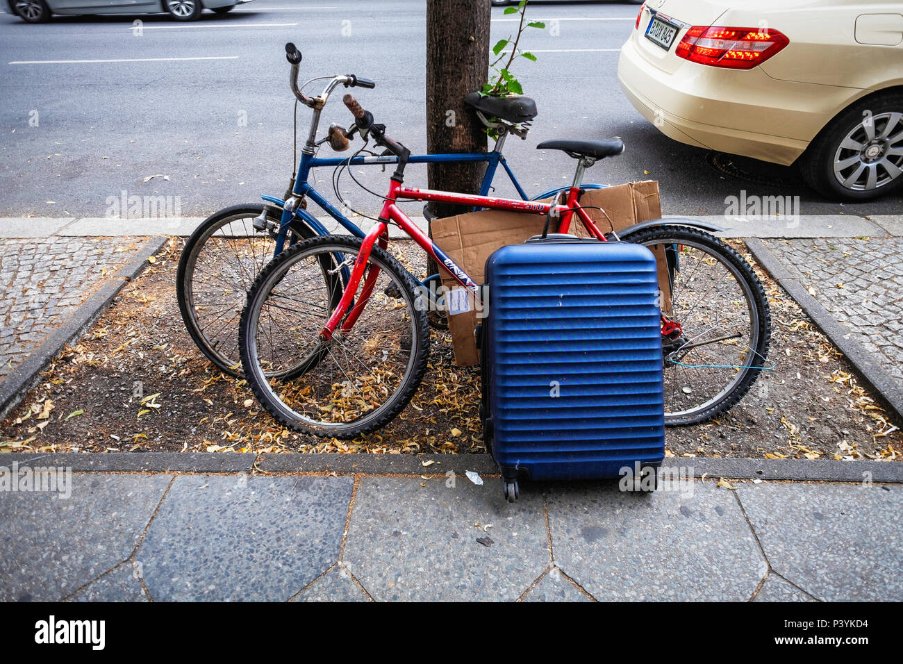 Possessions of the well equipped tourist - Bicycle, wheeled suitcase and spare wire coat hanger, Mitte,Berlin - Stock Image