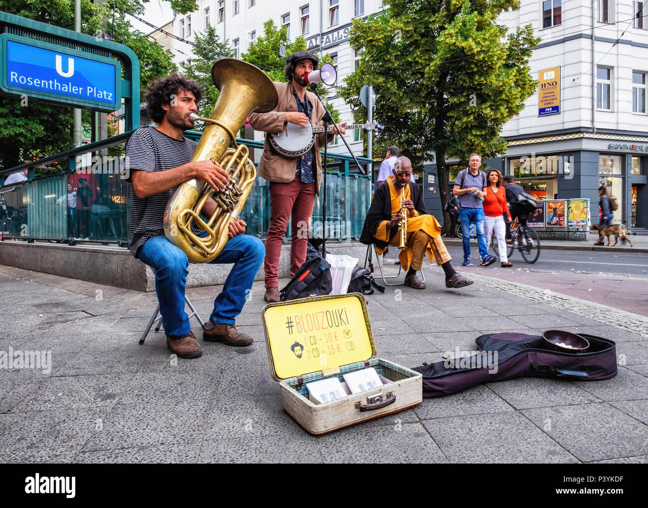 Three buskers play musical instruments & perform for passers-by on a warm Summer evening, Rosenthaler Platz, Mitte, Berlin - Stock Image