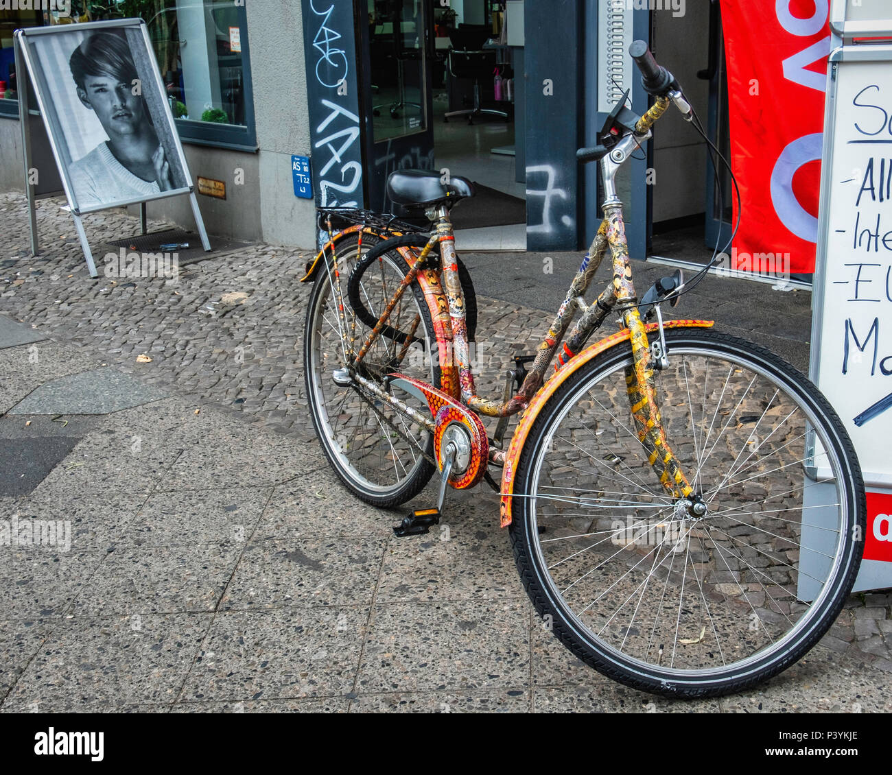 Berlin-Kreuzberg Kottbusser Damm street view. Bicycle with intricate arty paintwork on city pavement - Stock Image