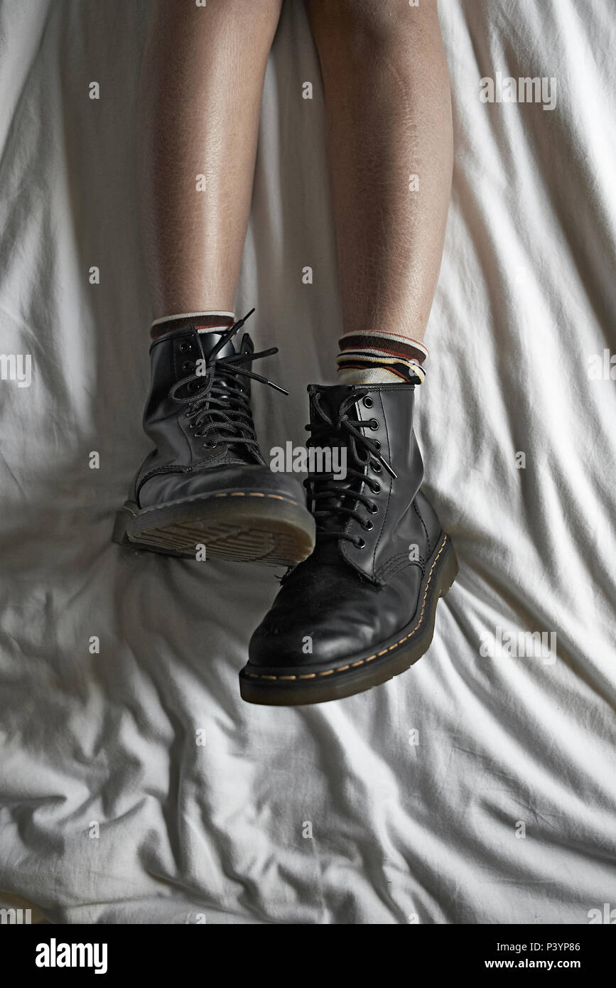 Top down shot of a teengirl's legs chilling in bed wear her black dr marten shoes being a rebel - Stock Image