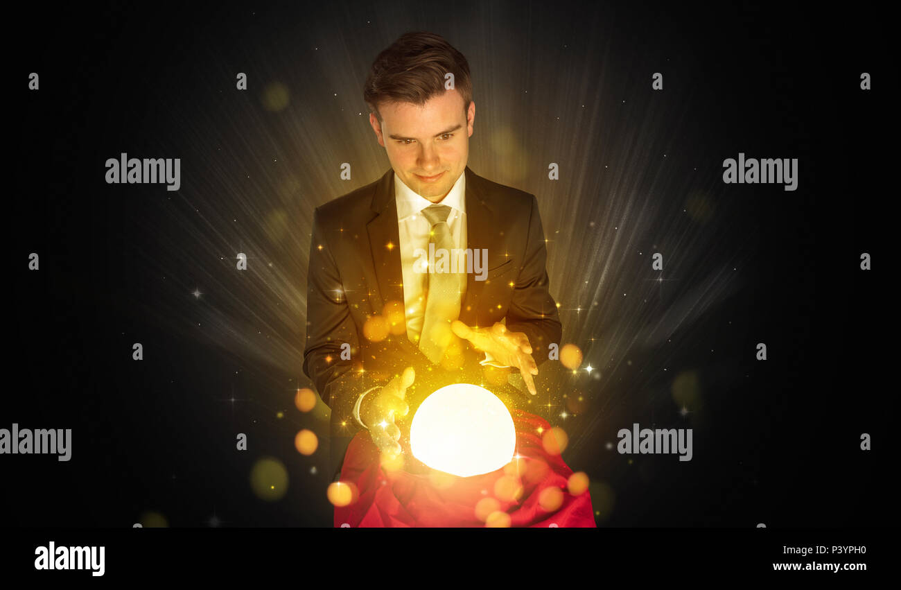 Gorgeous businessman sitting with sparkling magic ball in his lap  - Stock Image