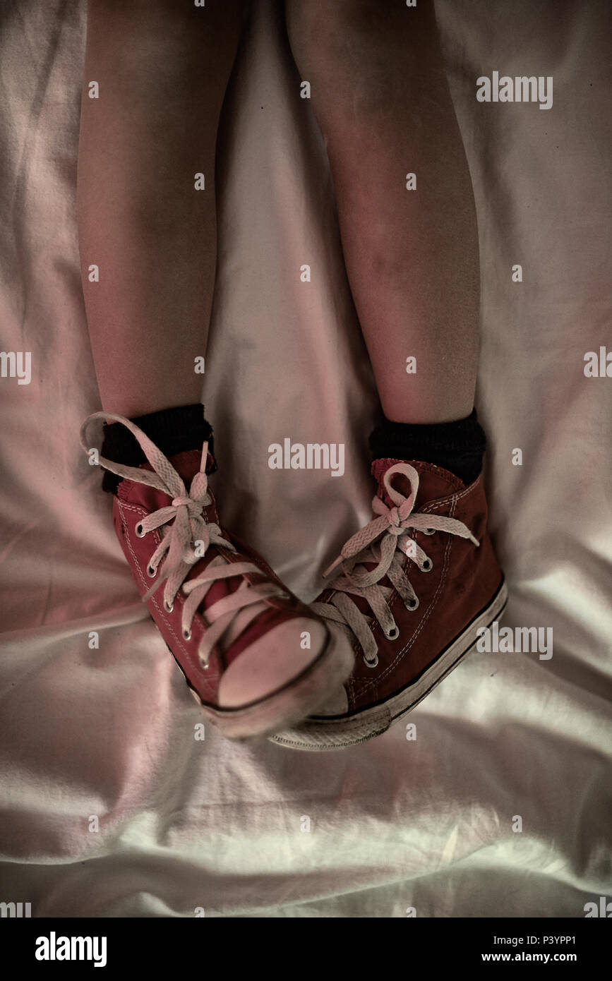 Top down shot of a teengirl's legs chilling in bed wear her red converse shoes being a rebel - Stock Image