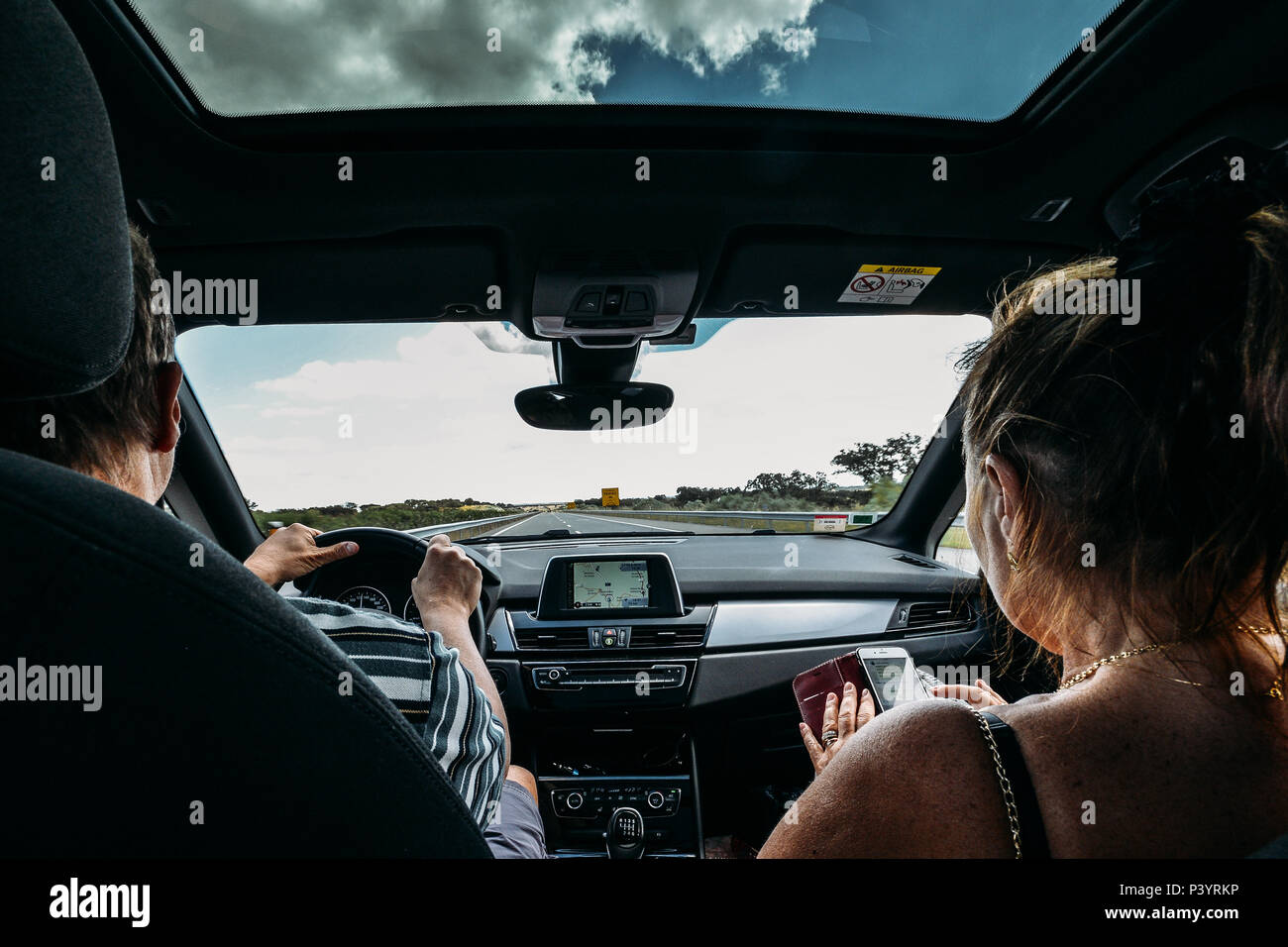 Older couple on front seat of car. Road trip concept. Woman uses a smartphone to pass the time while man drives - Stock Image