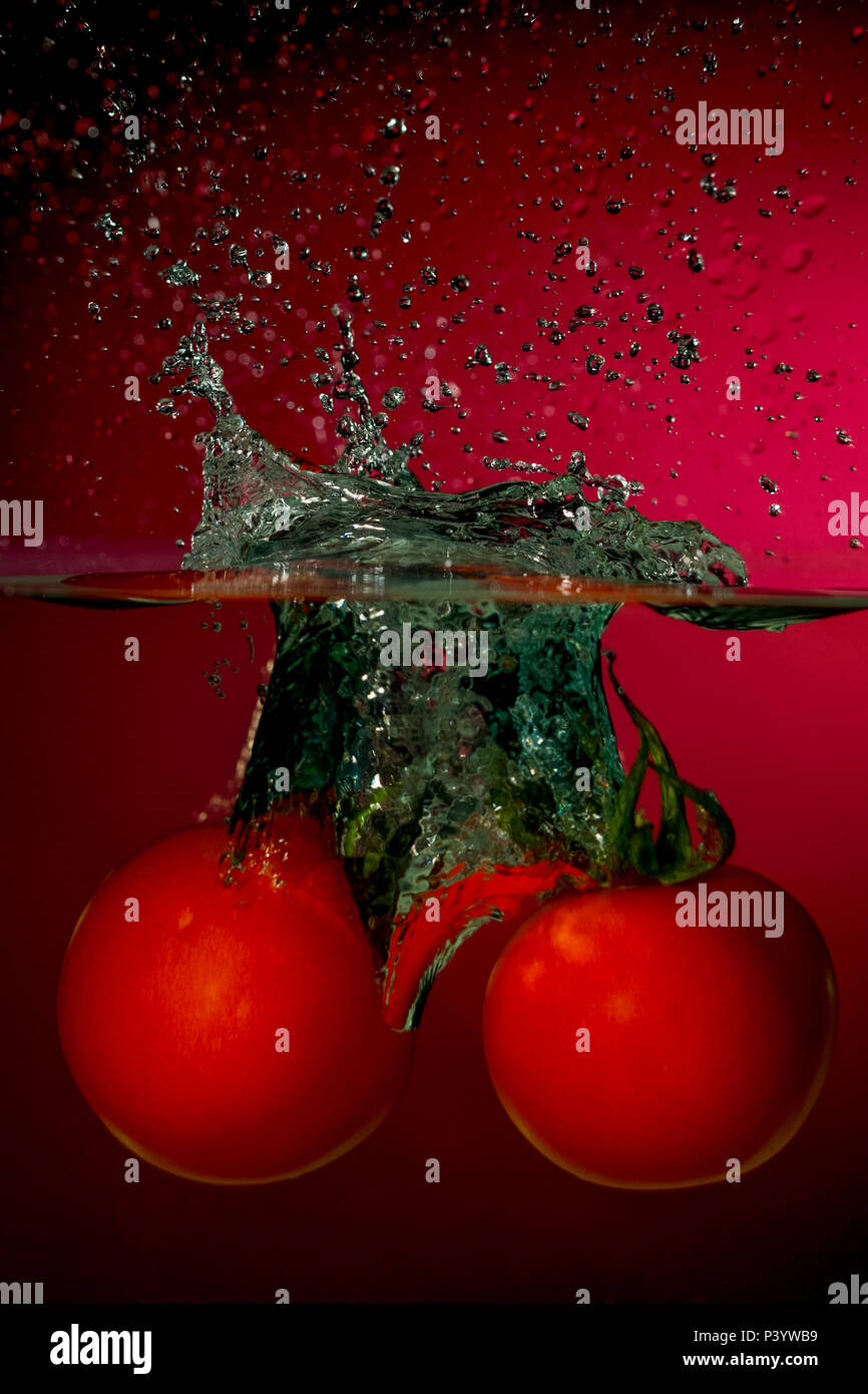 Red Tomatoes falling into the water and splashing drops - Stock Image