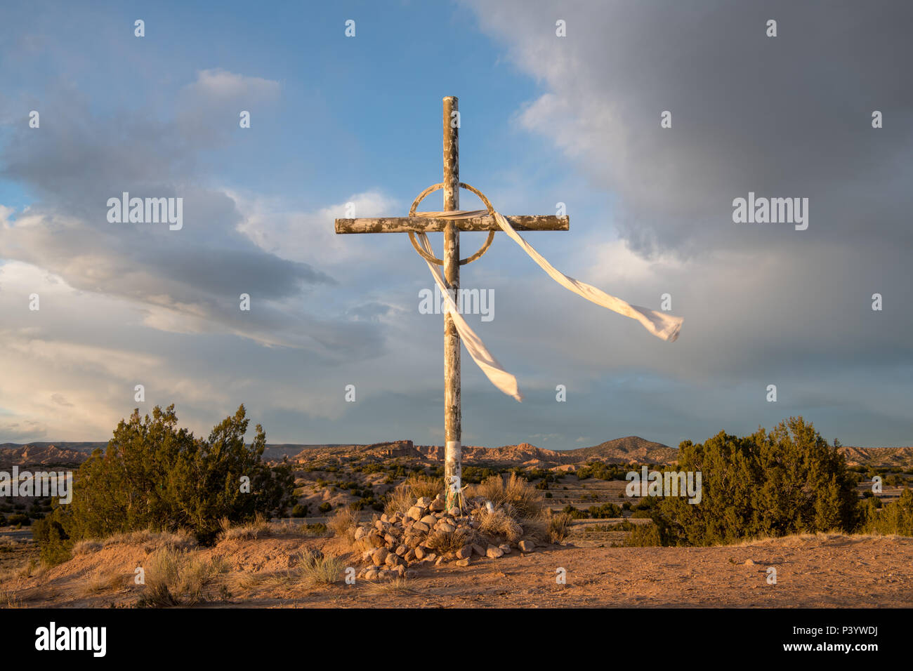 Cross under dramatic sky and clouds in the high desert landscape on the pilgrimage route from Santa Fe, New Mexico to the Sanctuario de Chimayo - Stock Image