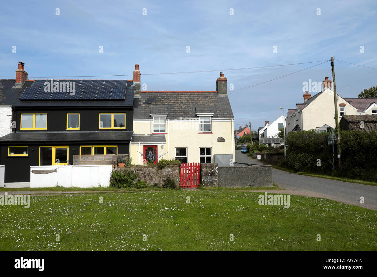 Modern house with photovoltaic cells and traditional cottage with red gate  in the village of Marloes in Pembrokeshire West Wales, UK  KATHY DEWITT - Stock Image