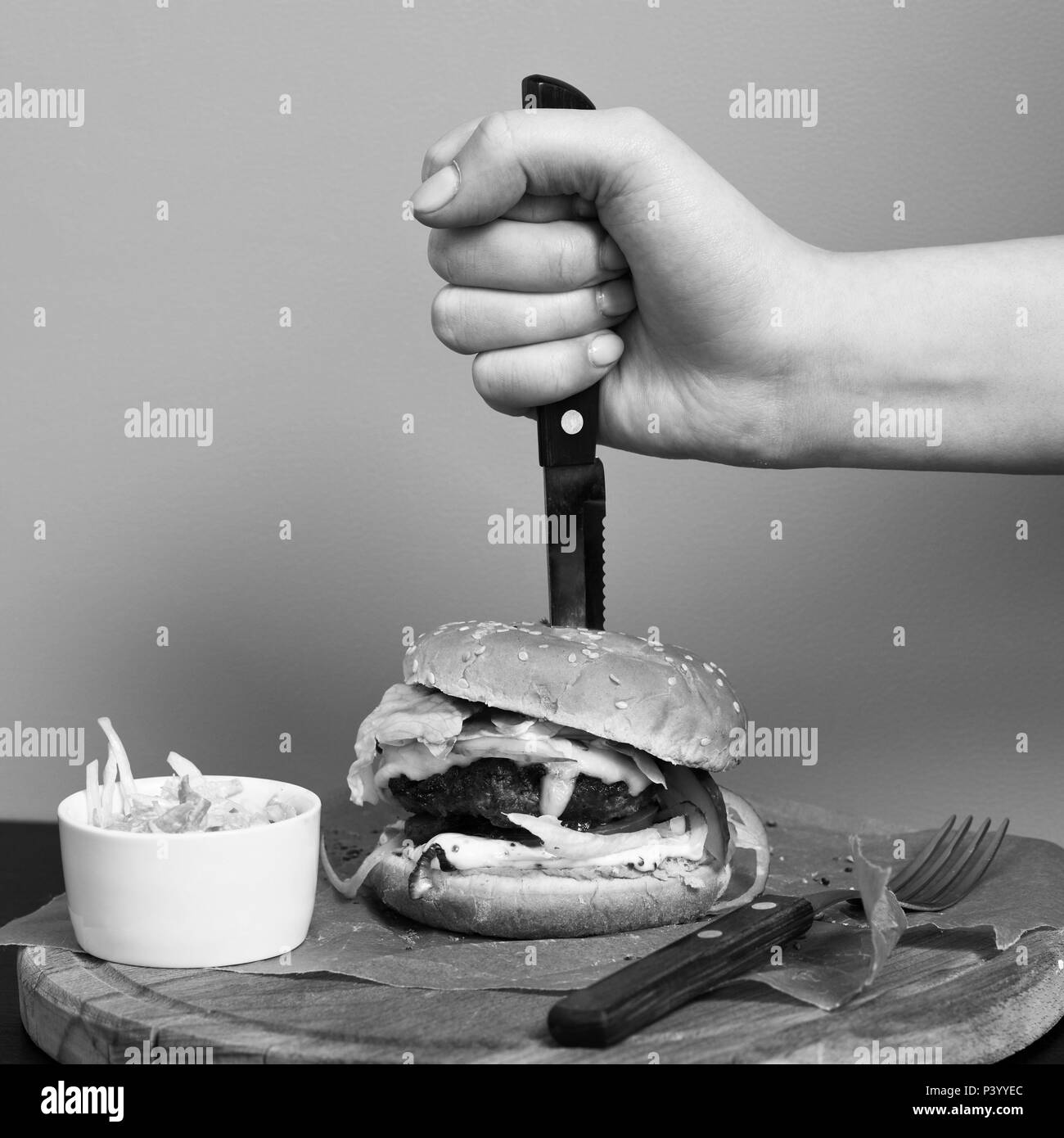 Hand stubbing burger with knife stock image