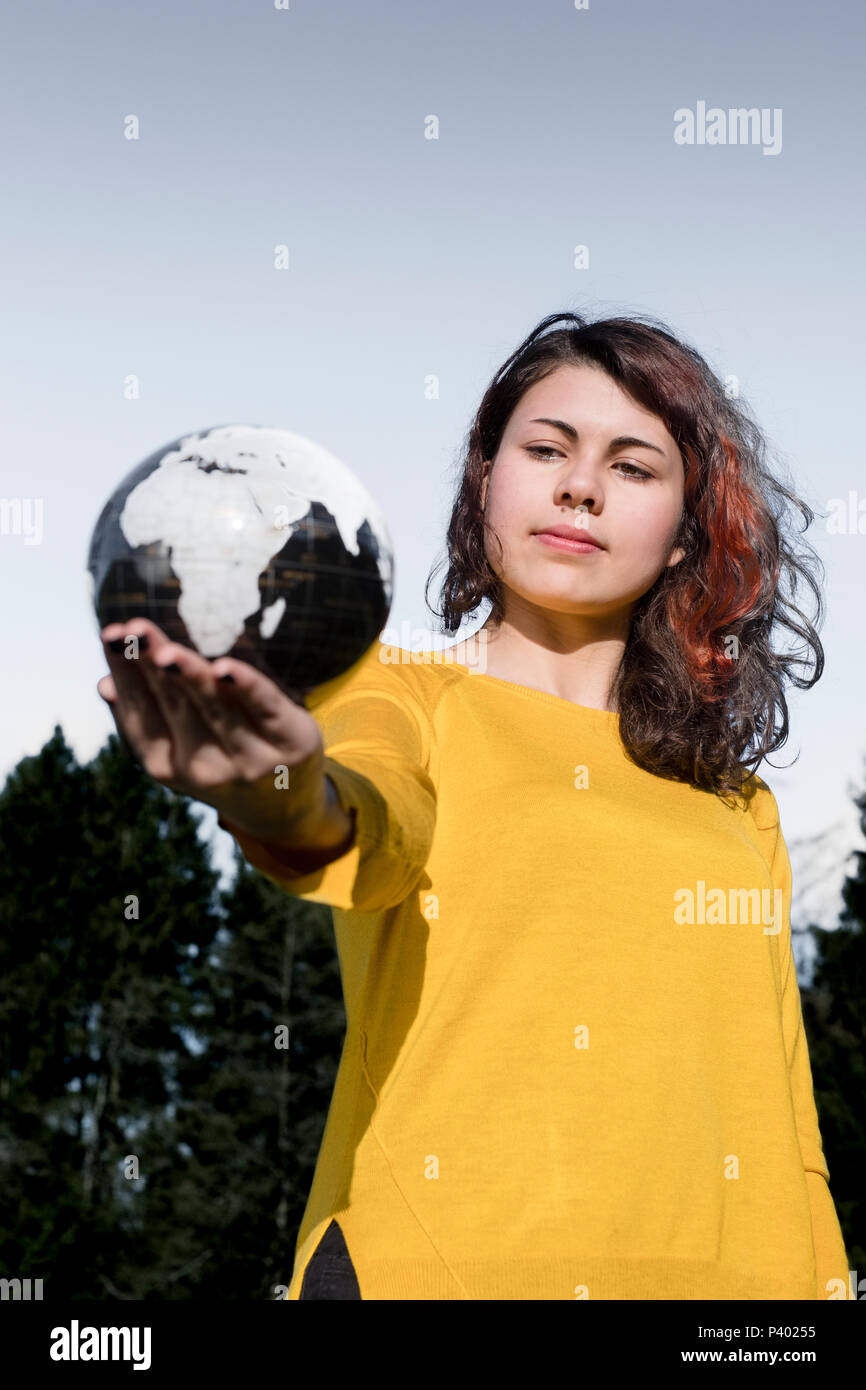 The whole world in her hand young woman in stylish yellow pullover the whole world in her hand young woman in stylish yellow pullover holding earth in her hand in front of sky and trees save the earth concept gumiabroncs Image collections