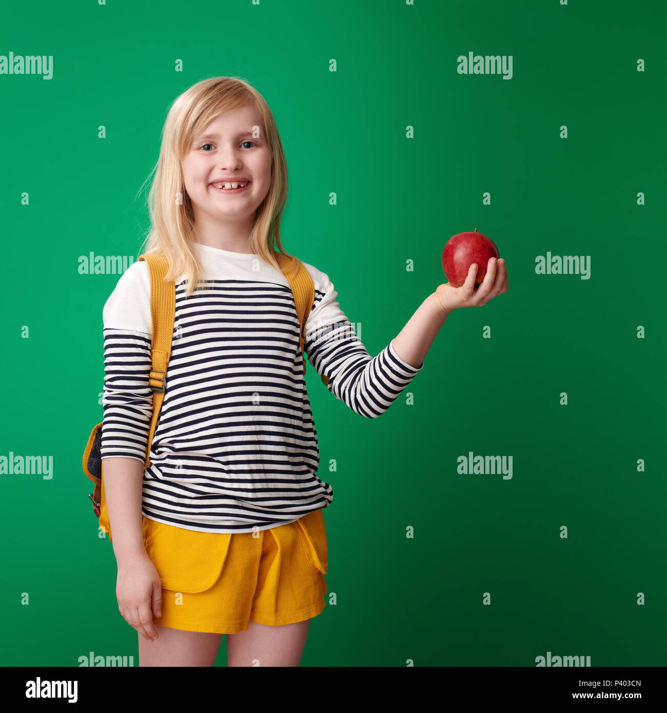 411dc05d2cac smiling school girl with backpack holding an apple against green background  - Stock Image