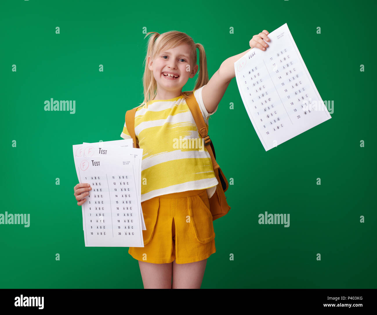 smiling school girl with backpack showing an excellent grade test after several failures on green background - Stock Image