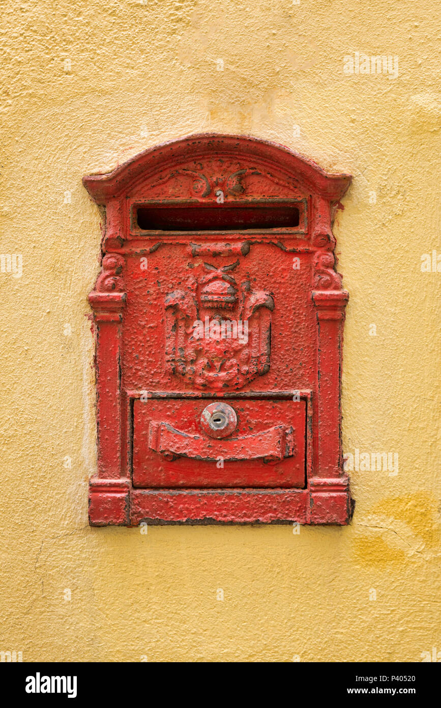 Old red Mailbox  cracked and rusting on yellow wall - Stock Image