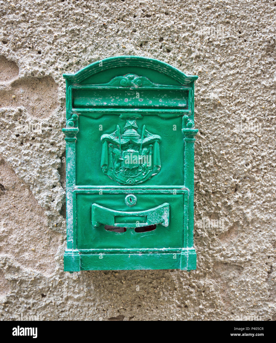 Old green Mailbox  cracked and rusting on old wall - Stock Image