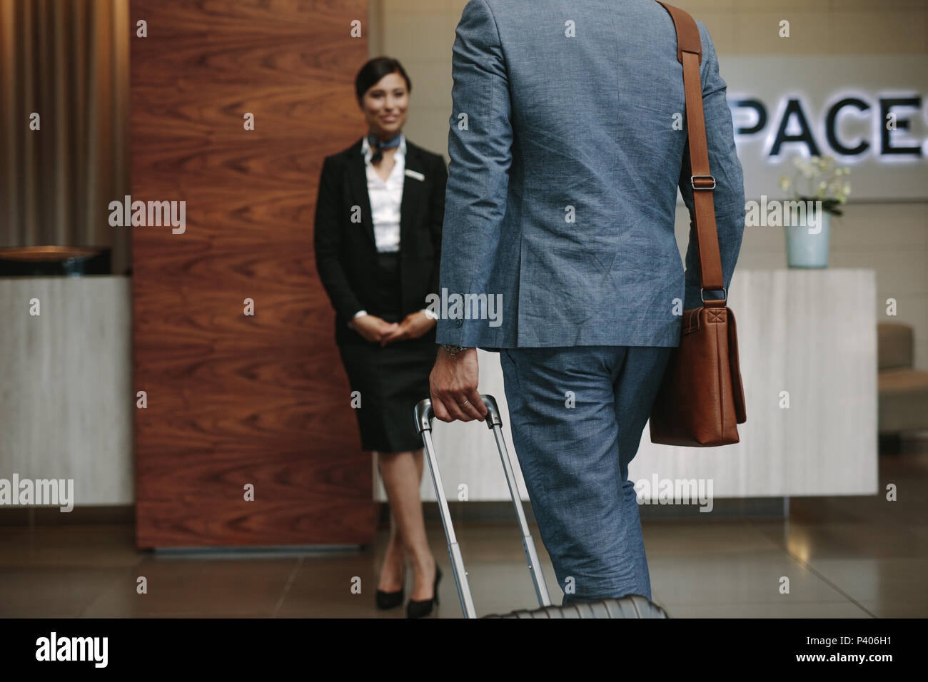 Businessman carrying suitcase and walking towards a receptionist waiting for welcome the guests. Business traveler arriving at hotel for conference. - Stock Image