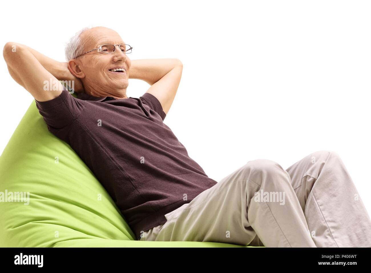 Relaxed senior sitting on a beanbag isolated on white background - Stock Image