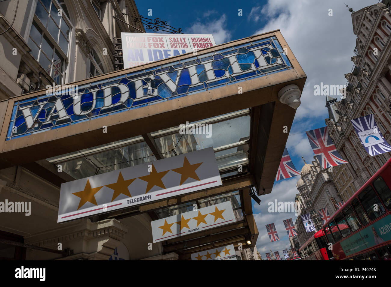 the vaudeville theatre in the strand, central London beneath blue sky and union flags flying across the street. acting and stage productions west end. - Stock Image