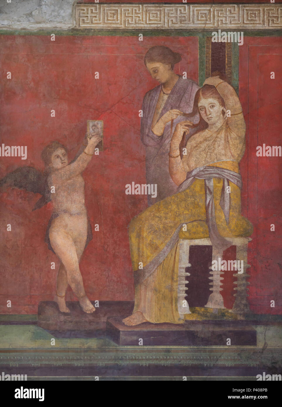 Dionysian Mysteries (Bacchian Mysteries) depicted in the Roman fresco in the triclinium (Roman dining room) in the Villa of the Mysteries (Villa dei Misteri) in the archaeological site of Pompeii (Pompei) near Naples, Campania, Italy. Initiation rite from the mysterious cult of Dionysus (Bacchus) is probably depicted in the murals. This fresco shows the initiate after the rite being prepared while Eros holds up a mirror to her. Stock Photo