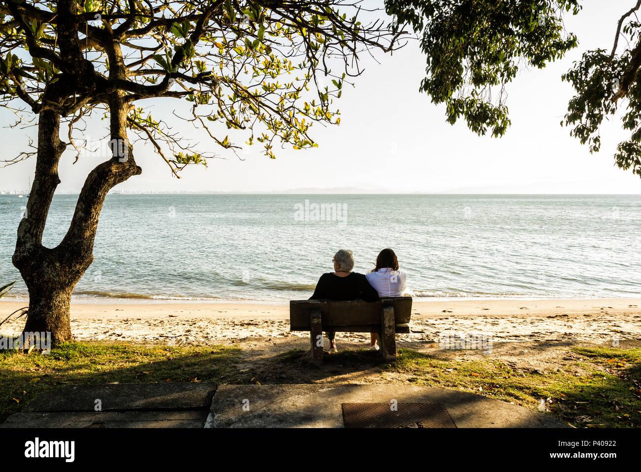 Mãe e filha sentadas em um banco na Praia de Santo Antonio de Lisboa. Florianópolis, Santa Catarina, Brasil. Stock Photo