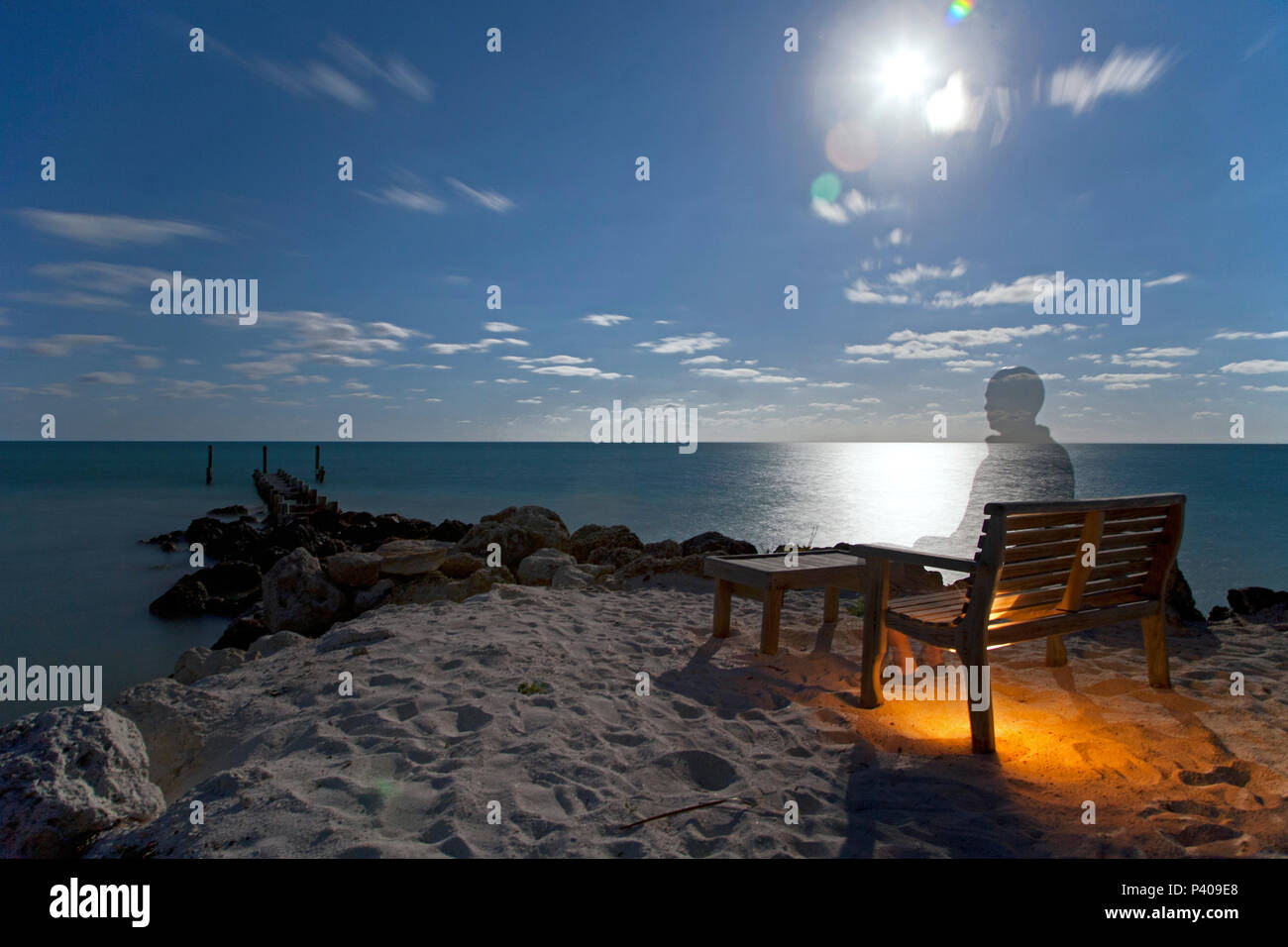 Ghost-Like Man Sitting on Beach at Dusk - Stock Image