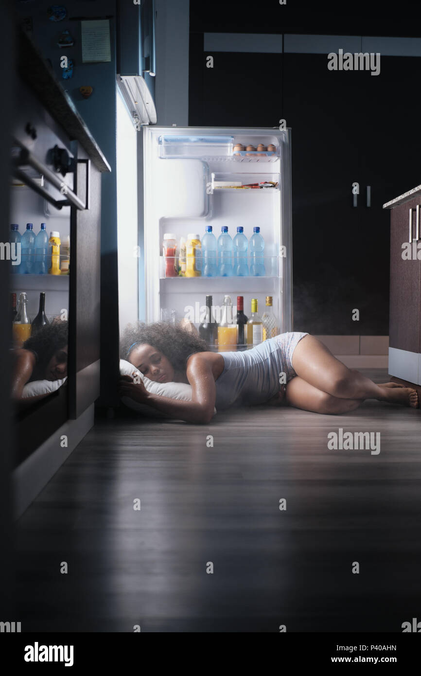 Black Woman Awake For Heat Wave Sleeping in Fridge - Stock Image