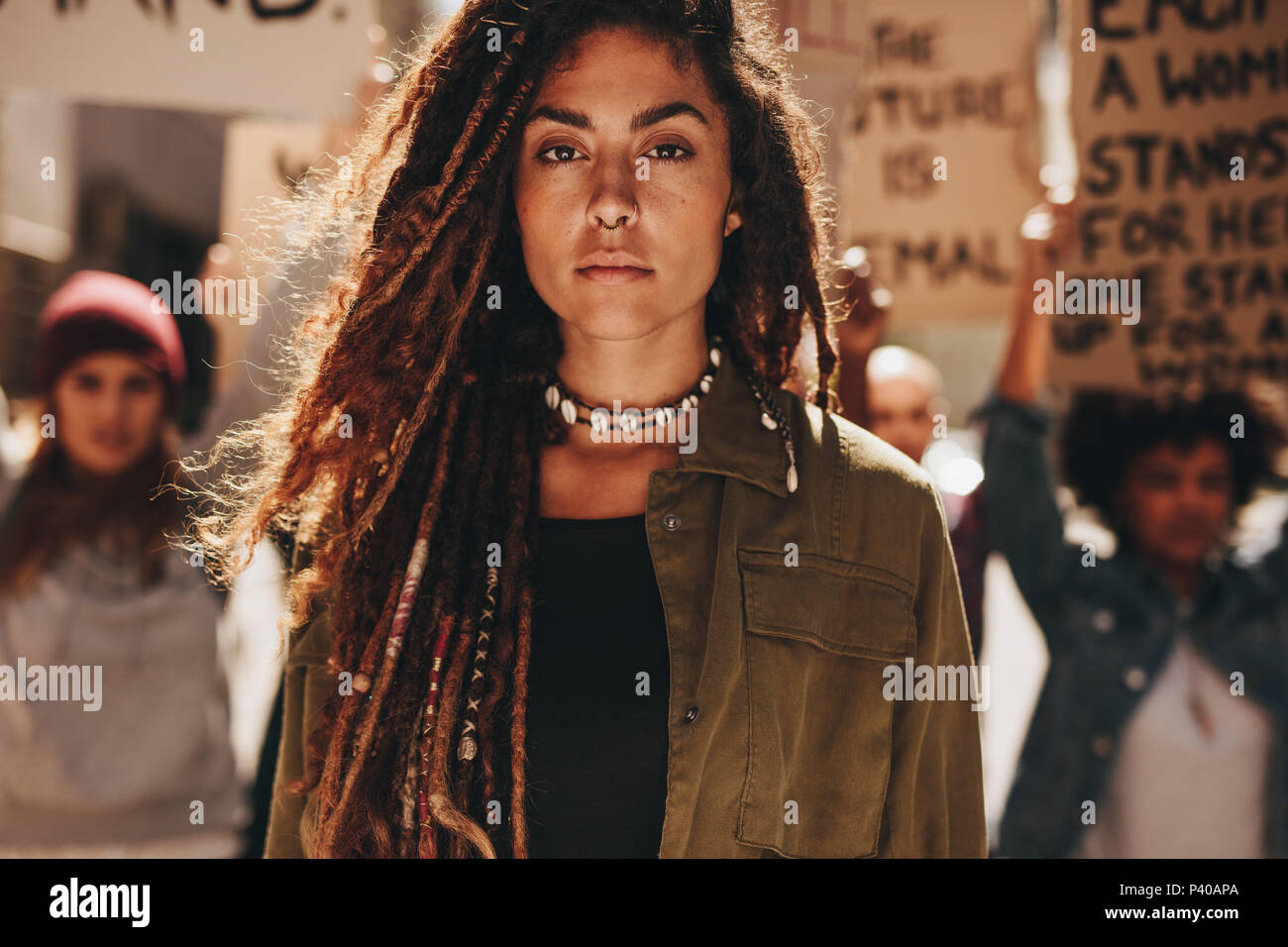 Woman standing outdoors in front of demonstrators on road. Female protesting with group of activists outdoors. - Stock Image