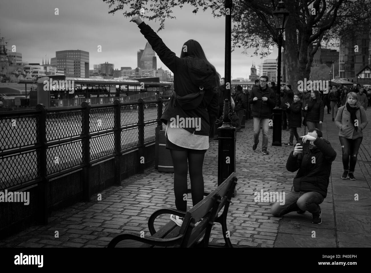 A young woman is being photographed by Thames - Stock Image