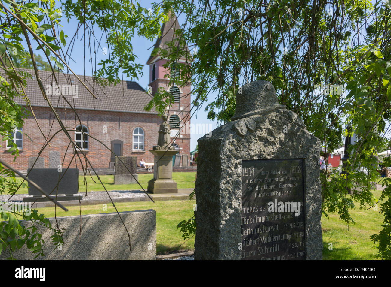 Memorial stone for the fallen of the 1st World War in front of the church Landschaftspolder, Bunde, Rheiderland, Ostfriesland, Germany. - Stock Image