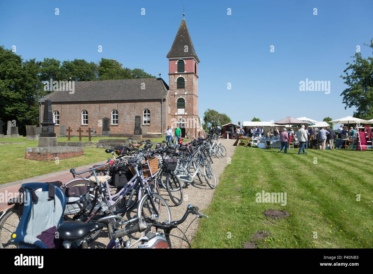 Bicycles stand in front of the church Landschaftspolder, Bunde, Rheiderland, Ostfriesland, Germany. - Stock Image