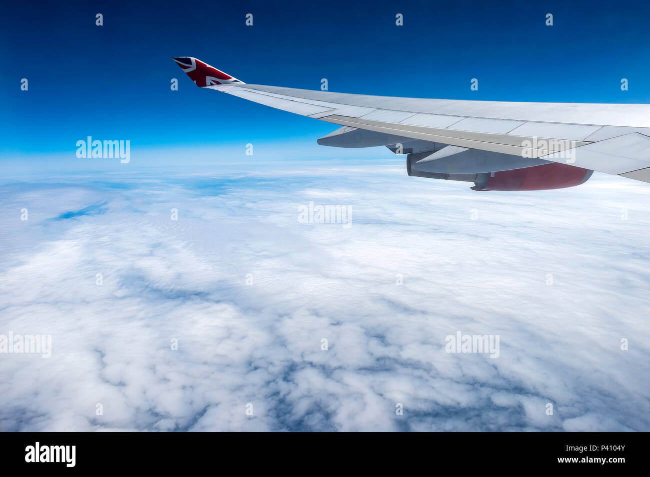 view from airplane window of the aircraft wing and engine with cloudscape - Stock Image