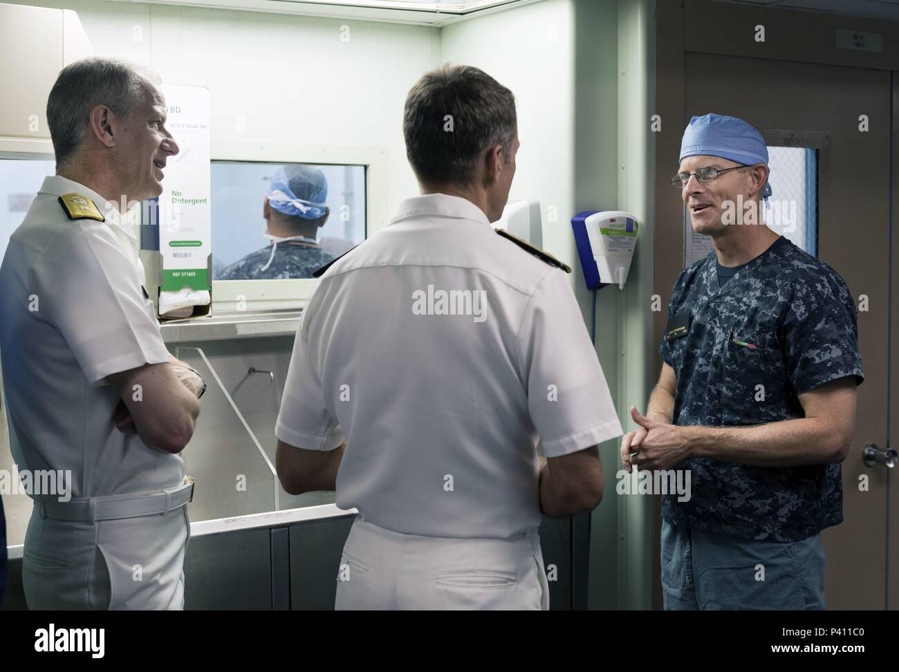 Photograph of three Navy officers, one wearing surgical scrubs, speaking with each other onboard the hospital ship USNS Mercy, in the waters off of Nha Trang, Vietnam, May 23, 2018. () Stock Photo