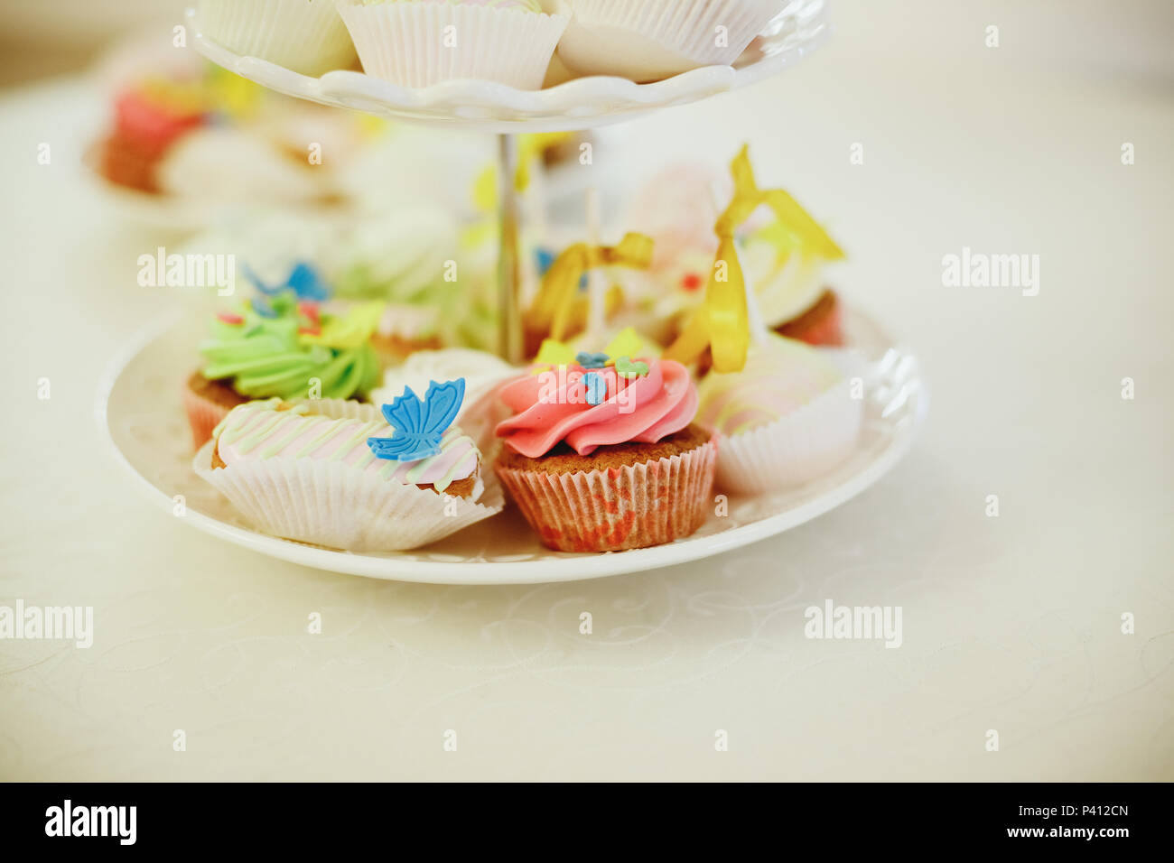Gourmet cupcakes with colorful buttercream frosting on white table.holiday picture, festive bakery. Toned image. Fresh baked homemade cupcakes.Decorative birthday cupcaces on cake stand.Copy space - Stock Image