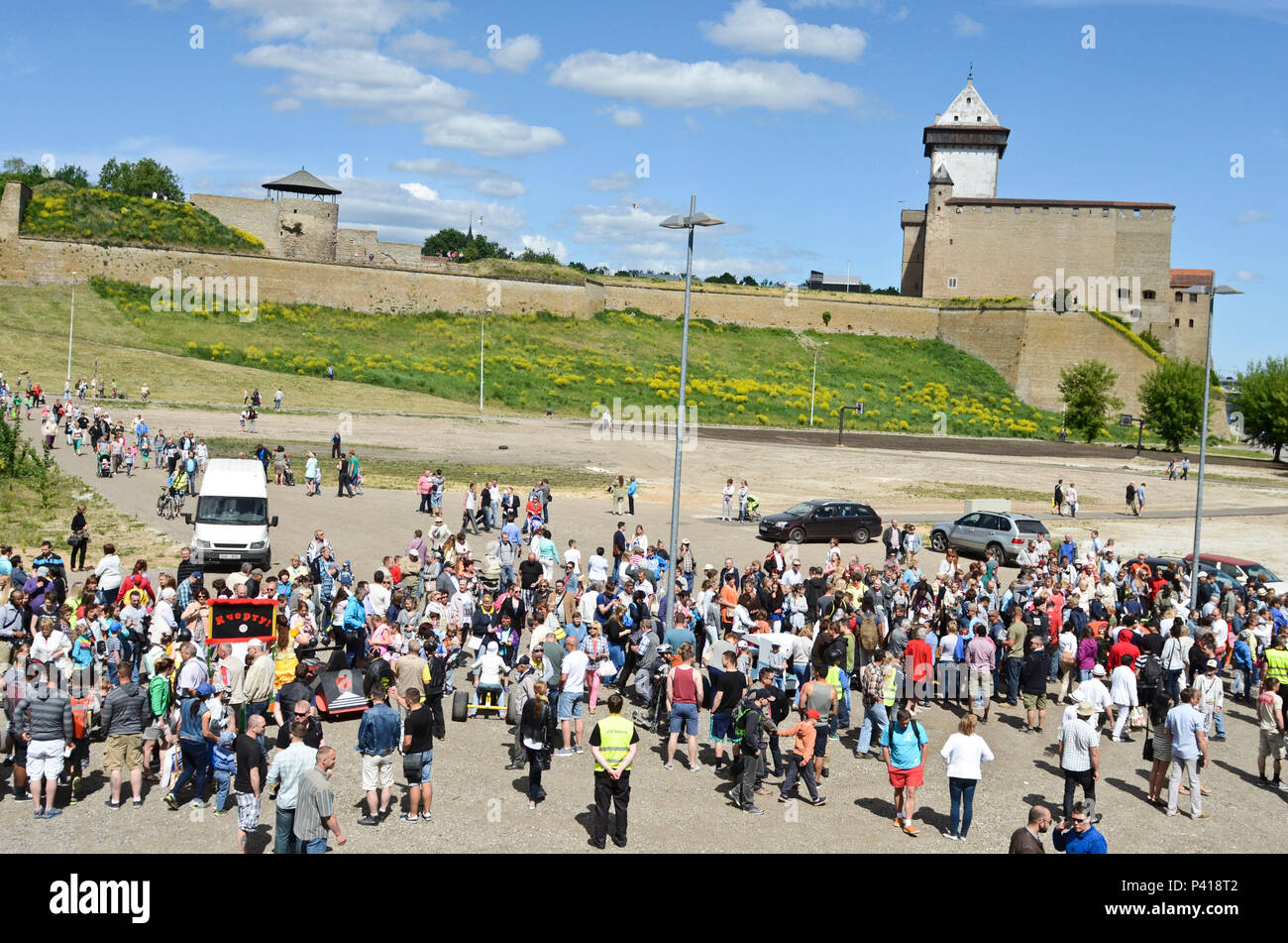 Estonian citizens gather around the contestants and their custom-made cars during a Soap Box Derby in Narva, Estonia, June 4, 2016. The Narva Castle is seen in the background. (U.S. Army photo by Staff Sgt. Steven M. Colvin) - Stock Image