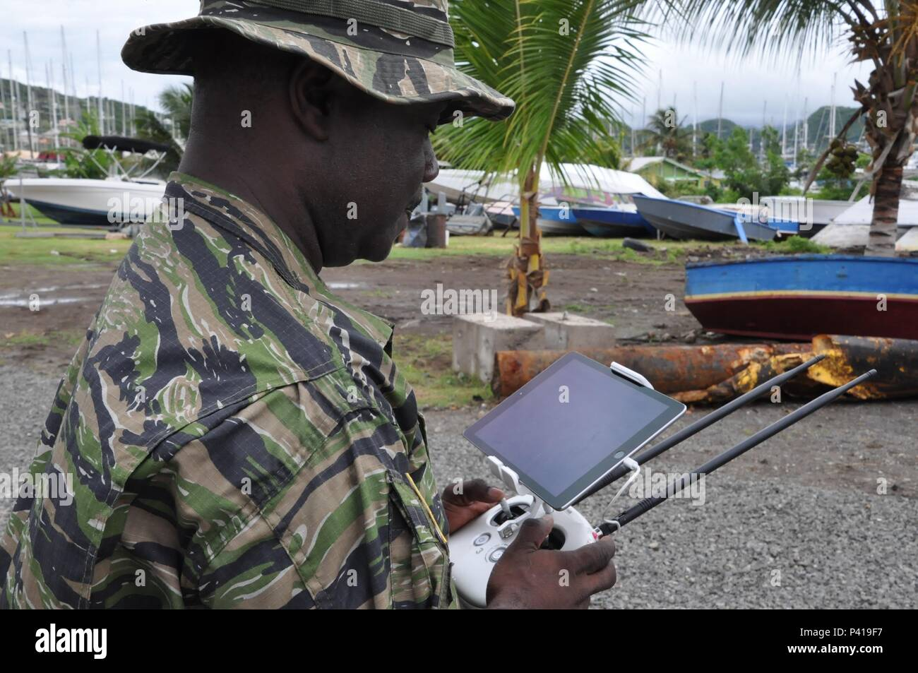 Lt. Regiwell A. Francis, from the St. Kitts and Nevis Defense Force, operates a drone June 6, 2016 in St. George's, Grenada, as part of Tradewinds 2016. Tradewinds 2016 is a joint combined exercise conducted in conjunction with partner nations to enhance the collective abilities of defense forces and constabularies to counter transnational organized crime and to conduct humanitarian/disaster relief operations.  U.S. Coast Guard photo by Petty Officer 1st Class Melissa Leake - Stock Image
