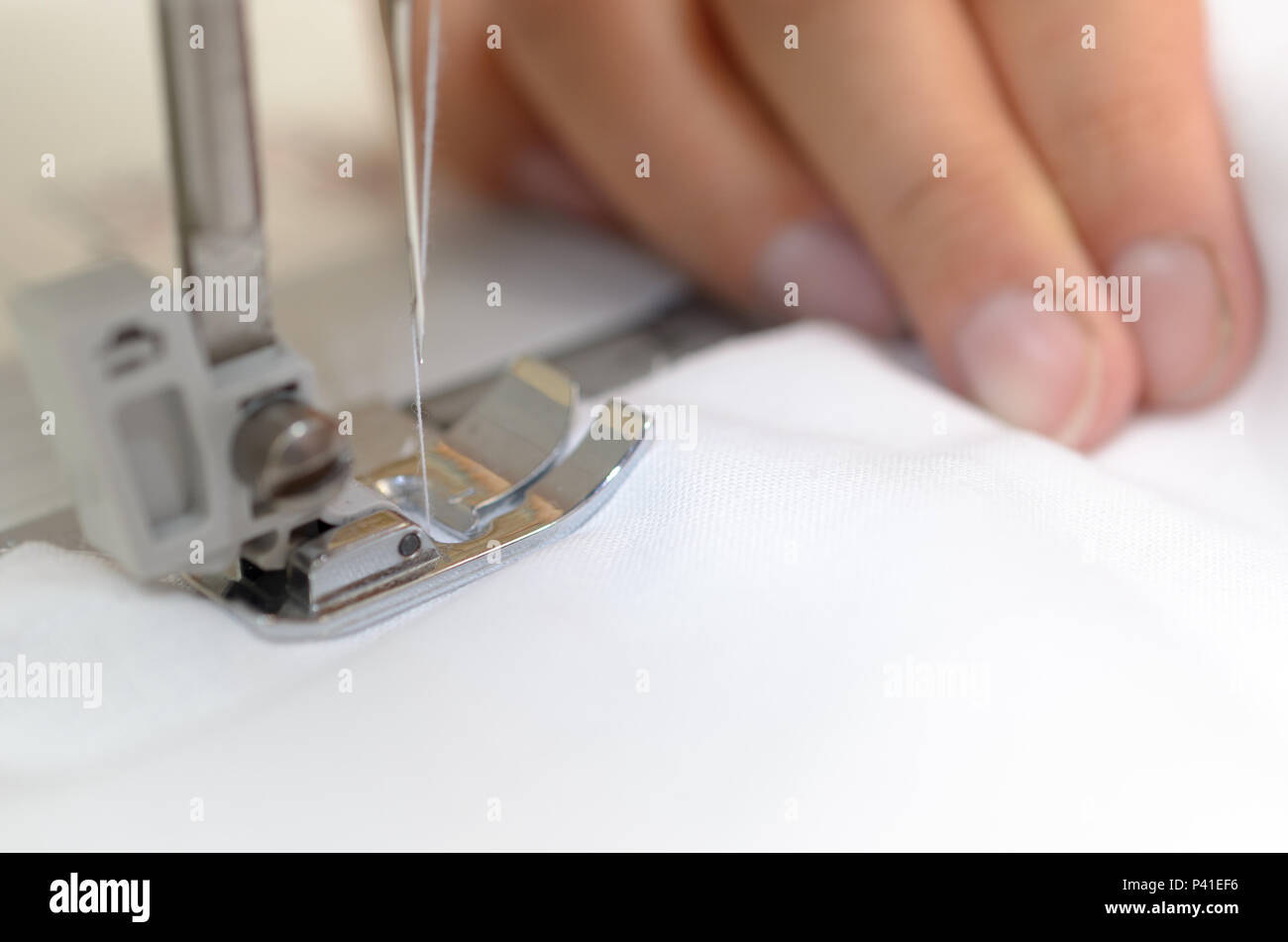 Hands seamstresses with white material behind the sewing machine - Stock Image