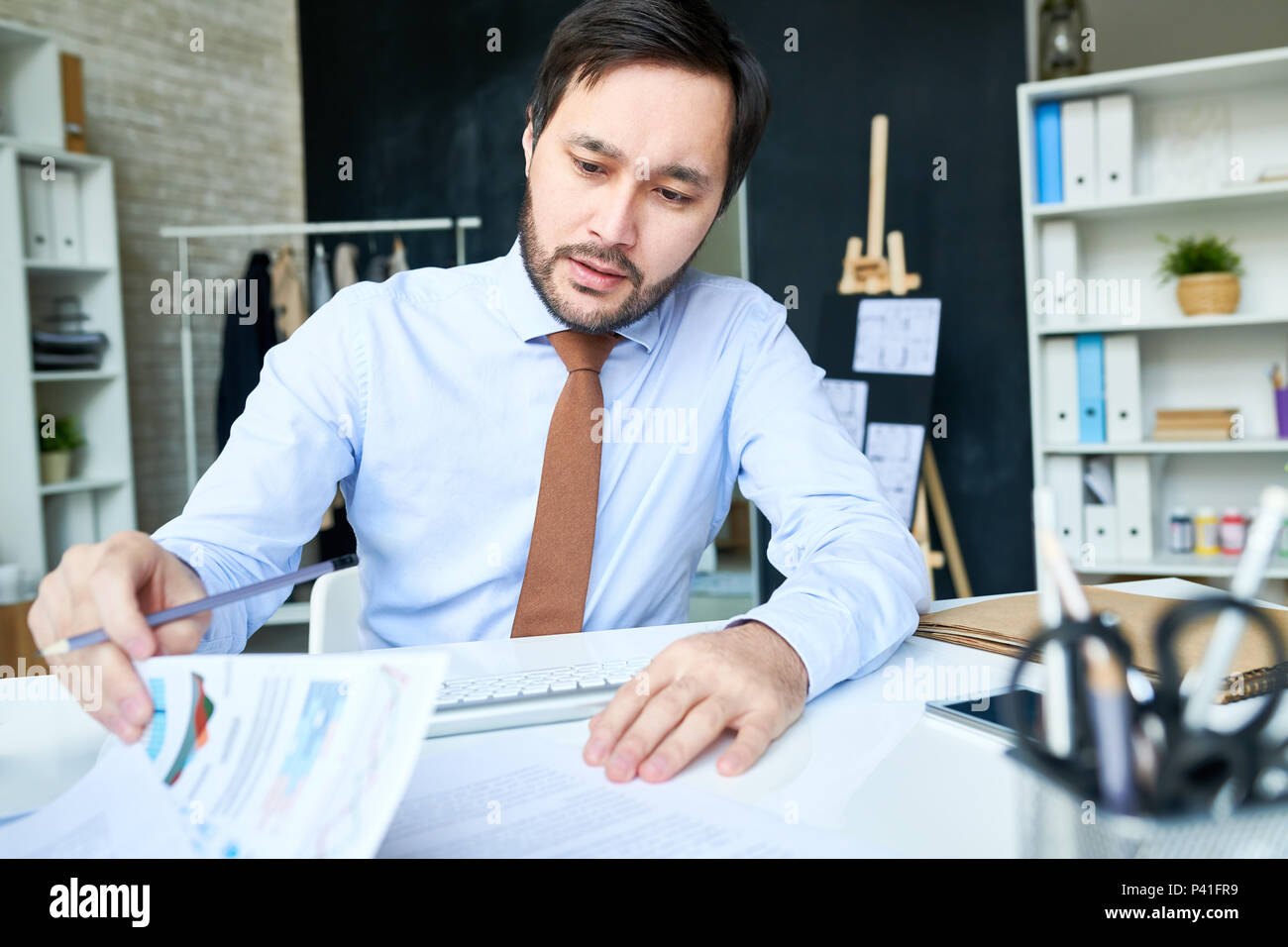 Businessman working with papers in office - Stock Image