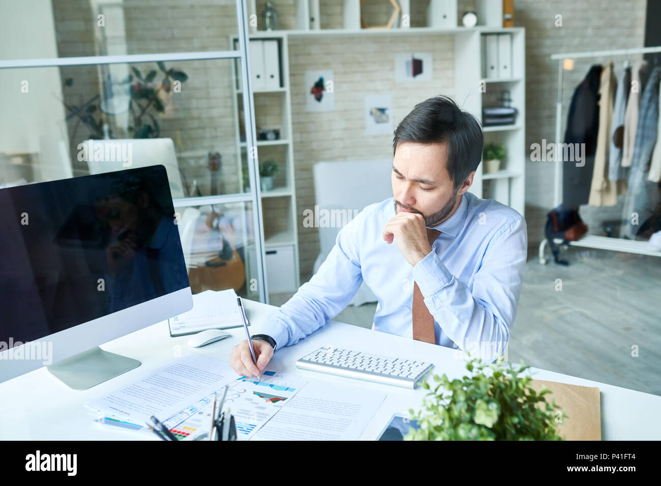 Thoughtful man working in office - Stock Image
