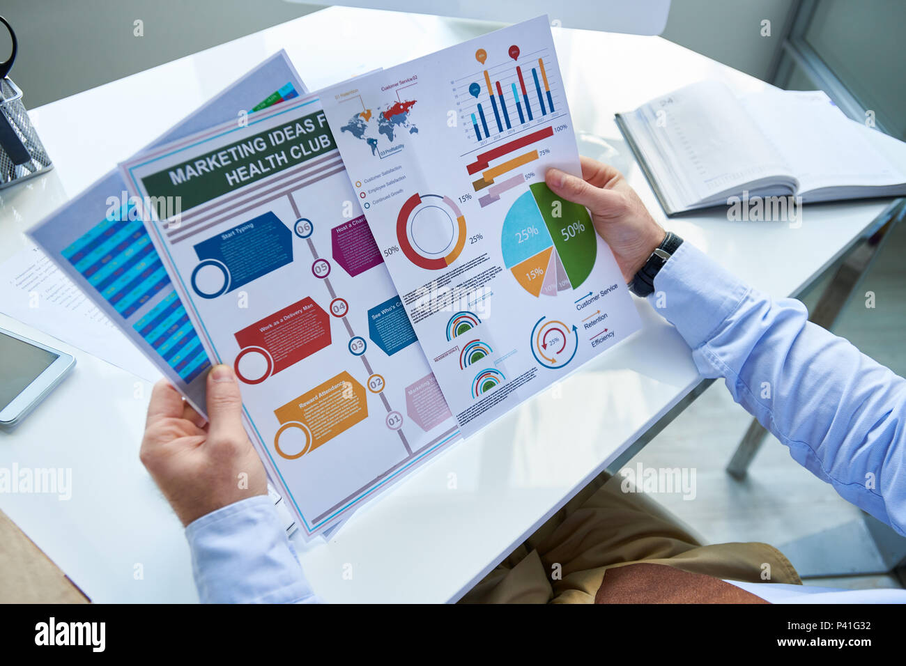 Crop businessman working with graphics - Stock Image