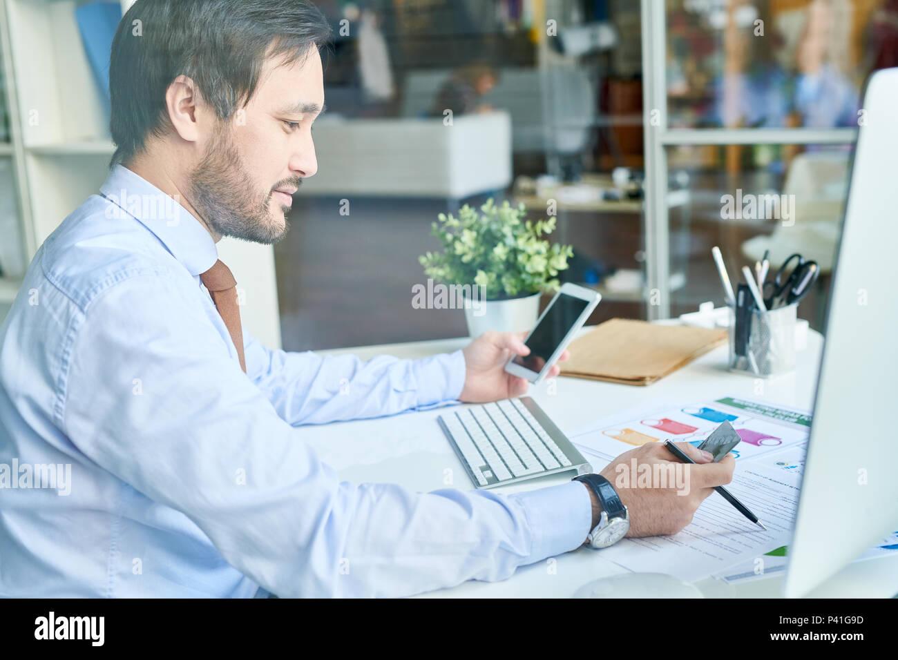 Man using phone and credit card - Stock Image
