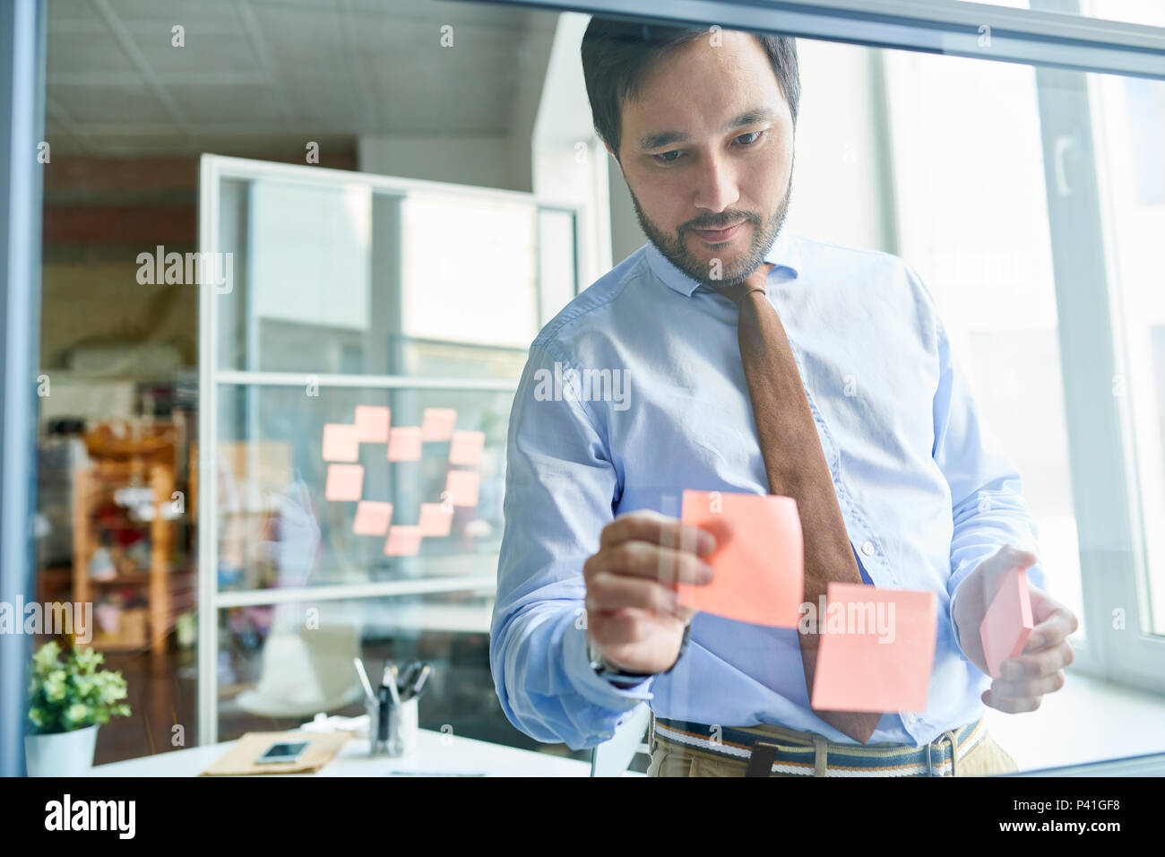 Creative man arranging stickers on board - Stock Image