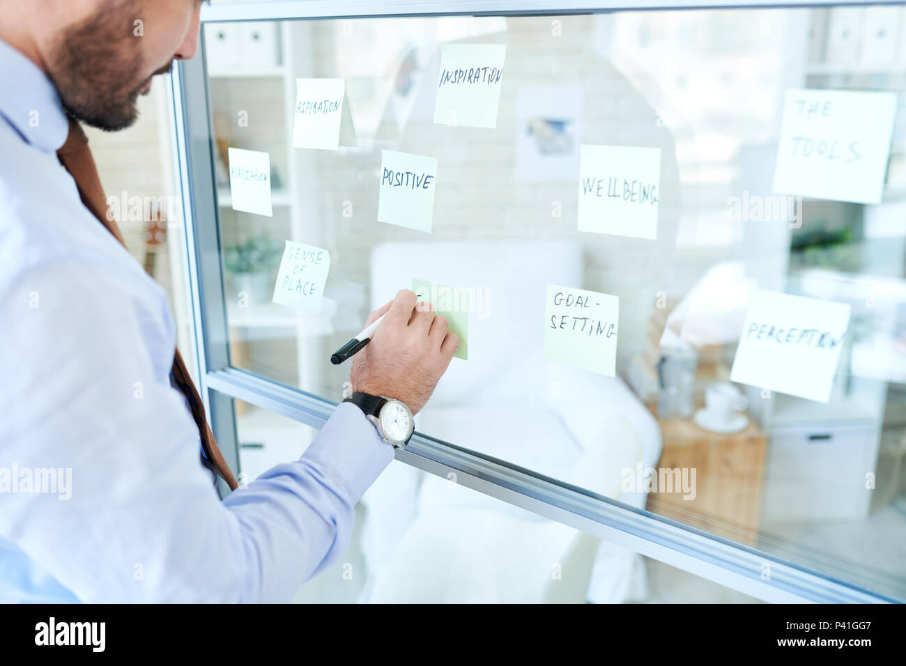 Man arranging stickers and making plan - Stock Image