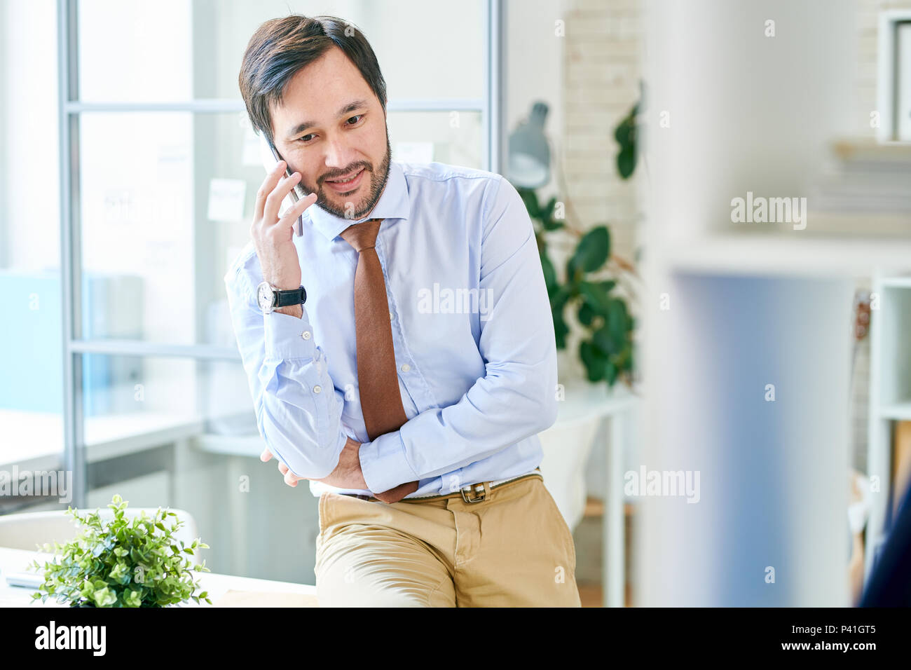 Content businessman having phone call - Stock Image