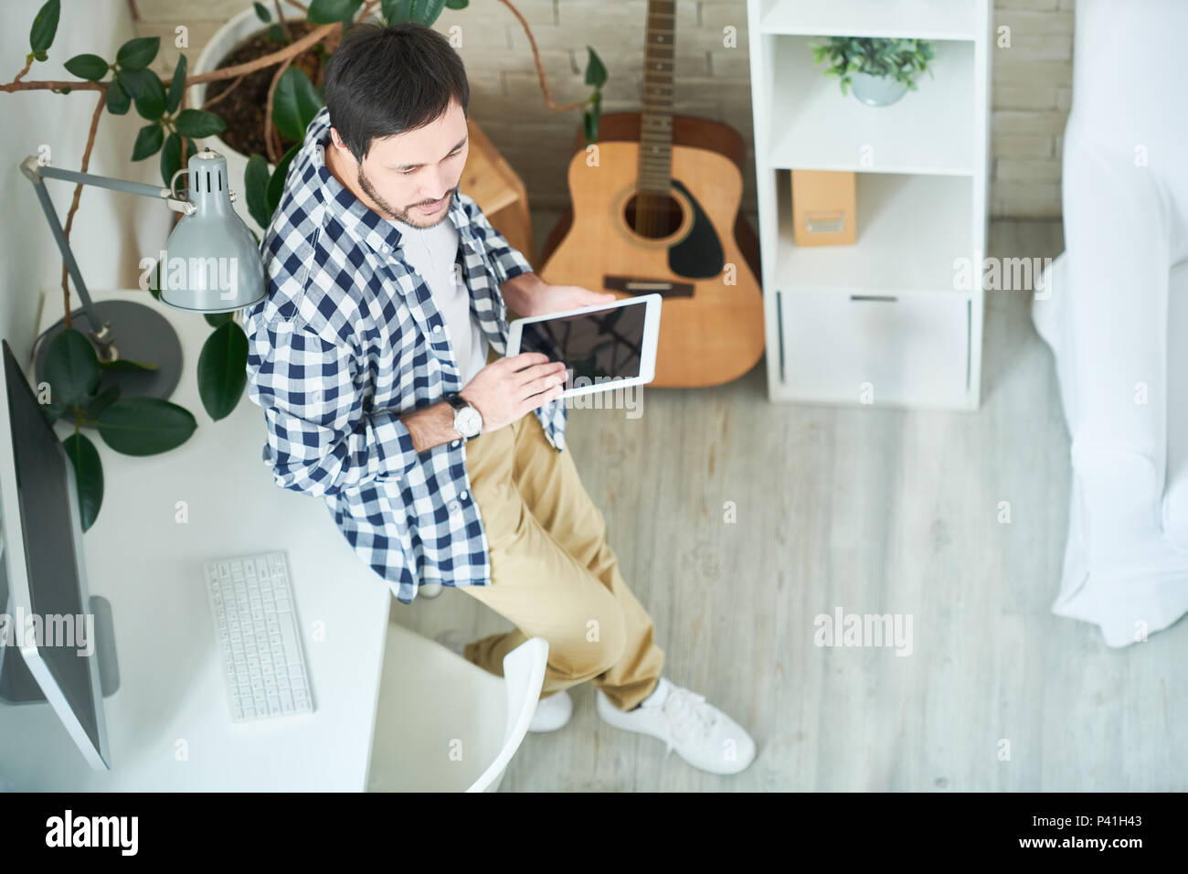 Creative man with tablet in studio - Stock Image