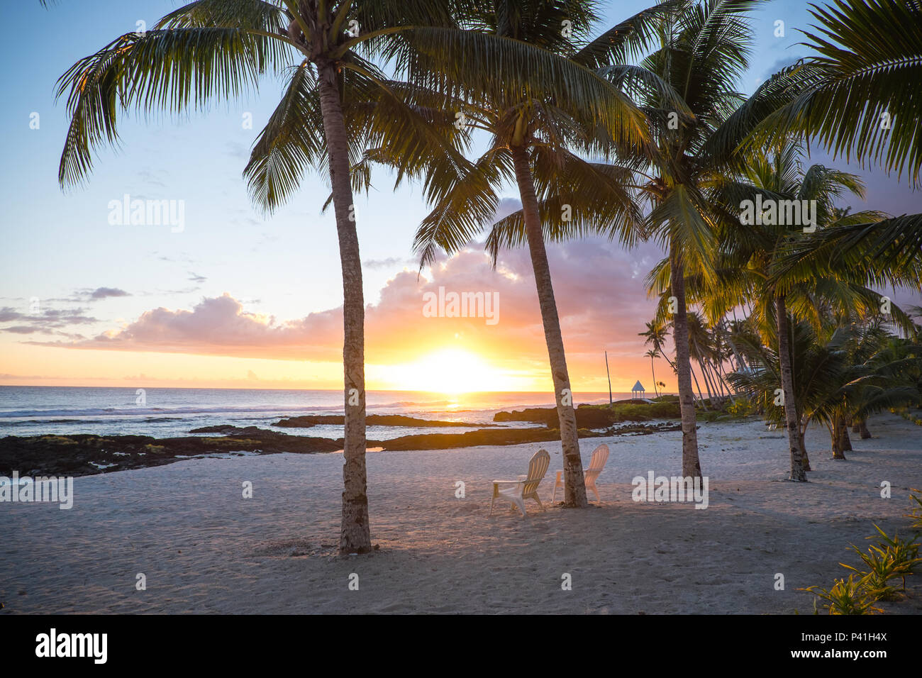 Two deck chairs under palm trees at sunset on an empty beach at Lefaga, Matautu, Upolu Island, Western Samoa, South Pacific Stock Photo