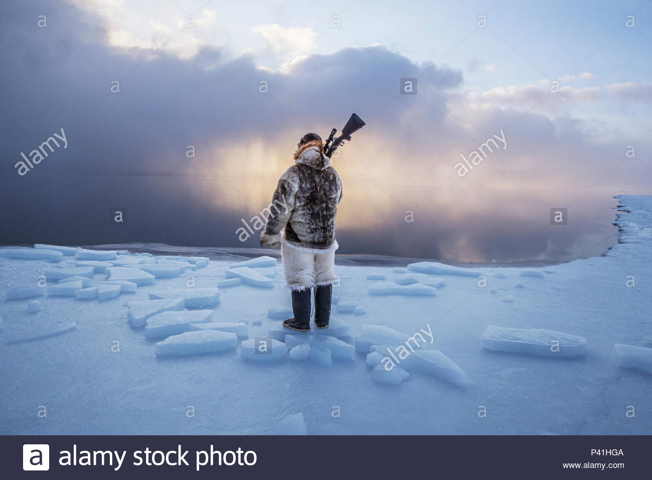 An Inuit hunter on the Arctic's shrinking sea ice. - Stock Image