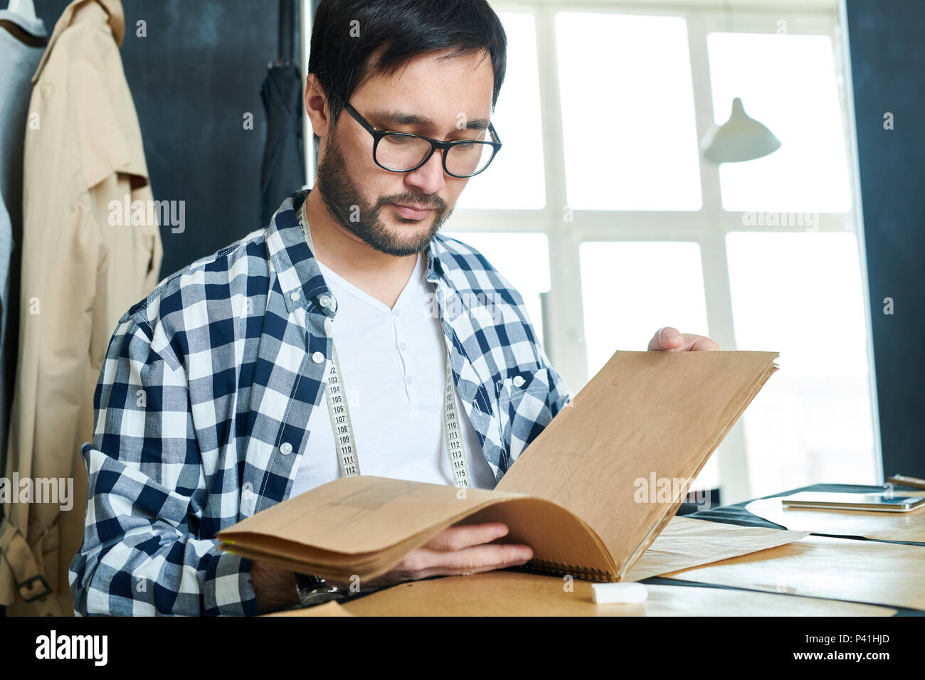 Man watching sketchbook with clothing models - Stock Image